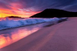 waves crashing on the beach at sunrise